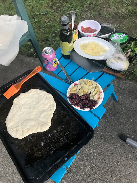 pizza dough on cookie sheet on small table, with dishes of topping on another small table