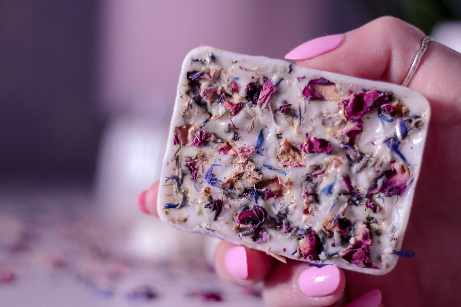 Close up photo of Ofaglasgowgirl holding the white beauty bar with pink rose petals in it