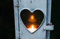Window of a wood burning stove in the shape of a heart. Fire inside