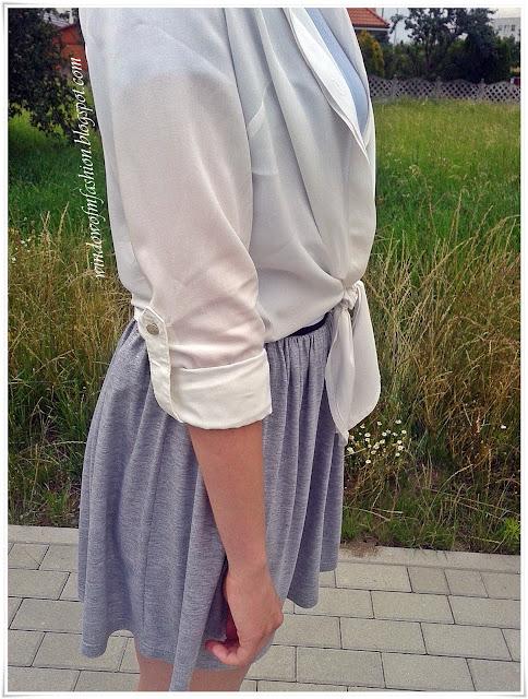 Biała wiązana koszula z podwiniętymi rękawami, szaro-srebrna spódniczka
