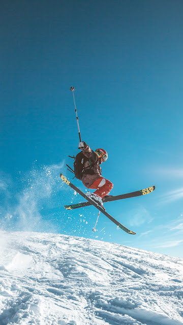 a skiier midair with their skis crossed and arms outstretched