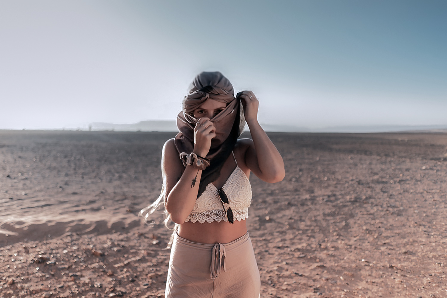 woman with covered face is standing in the dessert