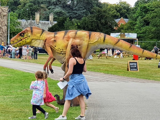 Image of Rent A Dinosaur green life size human controlled puppets roaming around Gloworm Children's Festival 2021
