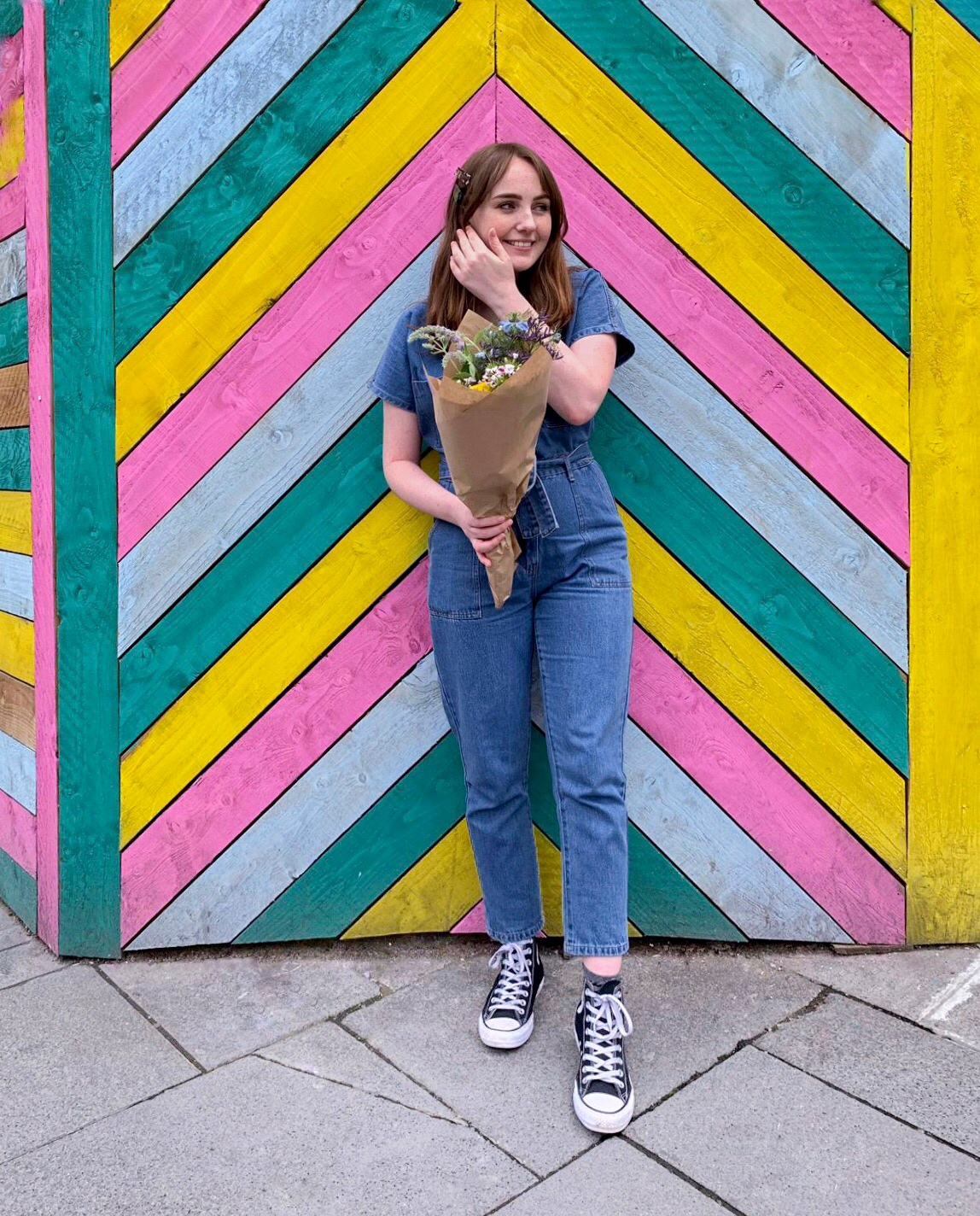 Liverpool blogger stands in front of brightly coloured striped wall, wearing denim boiler suit and converse, holding a bouquet of flowers and smiling