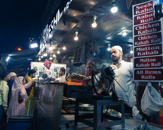 Person grilling meat at Qureshi kabab kebab Corner in Old Delhi India with people during ramadan ramzan ramazan