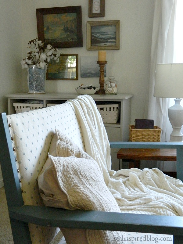 A cottage-like summer living room tour using whites, neutrals, and small pops of color in furniture and plants. Blue upholstered bench settee with sweater blanket and quilted pillow in front of gray dresser and sea gallery wall.