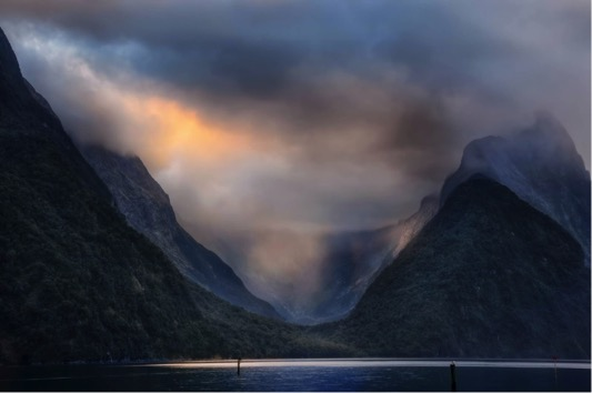 Clouds hanging over milford sound with two mountains and water between them