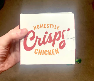 A photo of a white square box that contains a burger which says homestyle and burger in small orange font with crispy in large cursive orange font on a bright background