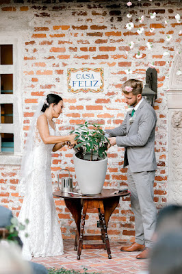 bride and groom watering plant during ceremony