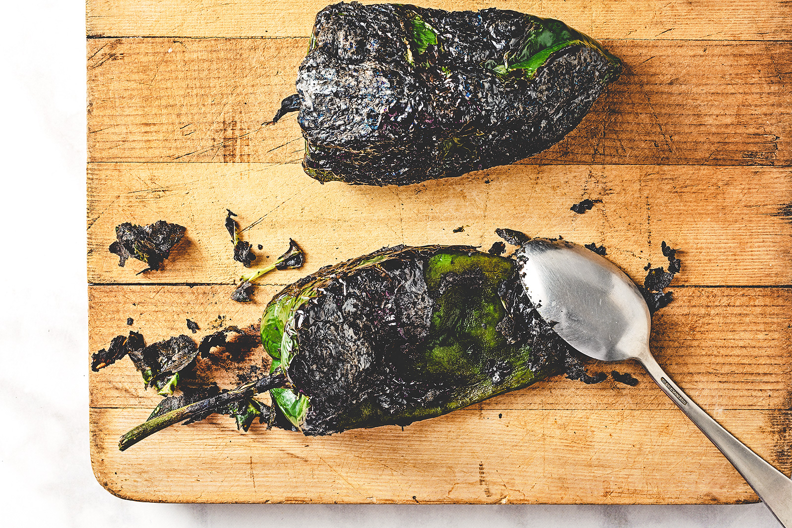 Use a spoon to scrape off the charred skin of a roasted poblano.