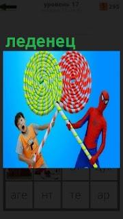 Мальчик и человек паук держат на палках большие и необычные леденцы