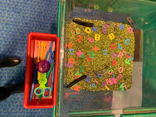 large sensory bin filled with dried peas and foam letters with tray of tweezers and strainers