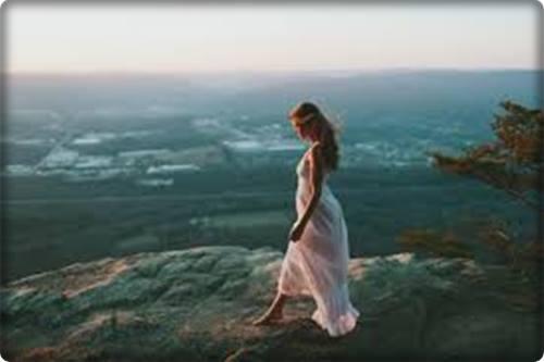Uma jovem descalça caminhando sobre as pedras, beirando o mar. A paisagem é sombria.