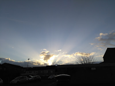 Sun shining up like God behind the clouds