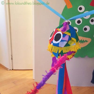 Buntes Monster aus Pappmaché mit Kreppbändern an einem Seil