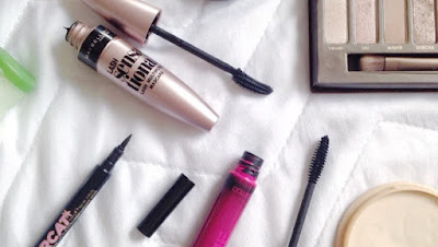 travel makeup flatlay of mascara, eyeliner, powder and eyeshadow
