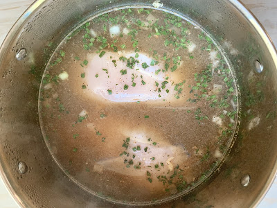 2 chicken breasts in broth in a pot