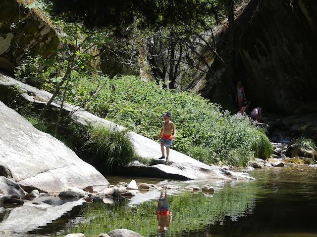 Niño en bañador al borde de un río