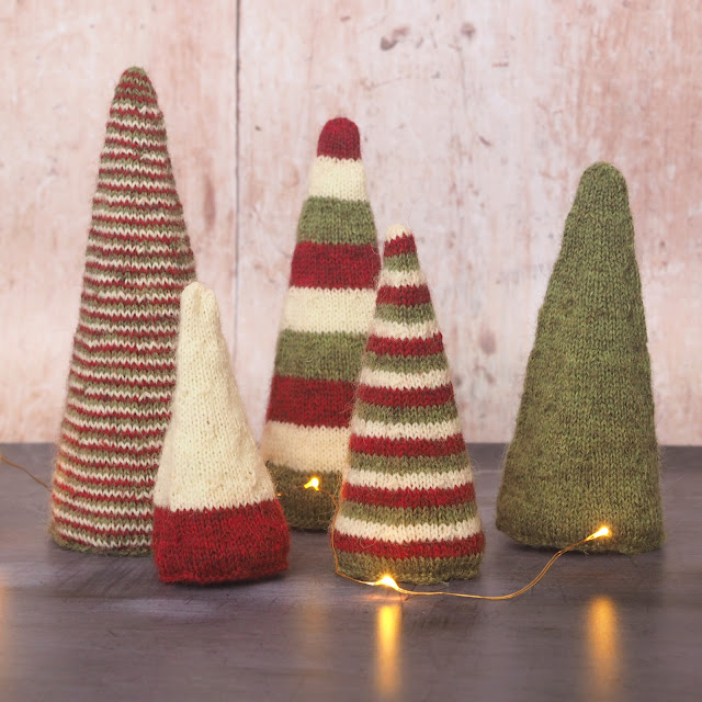 Five conical trees in red, green and cream