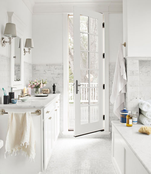 White bathroom with Carrara marble floors= in the form of a hexagon mosaic, counters and tub surround, a French door leads to a patio