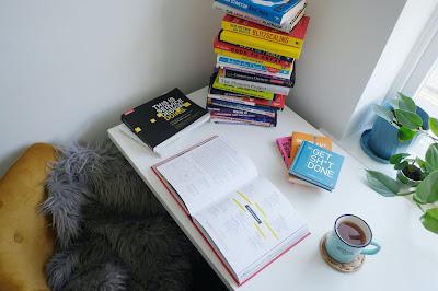 Kirjoja ja teekuppi työpöydällä