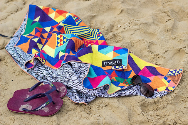 A colourful towel, flip flops and sunglasses on sand