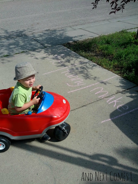 Preschooler driving in a red ride-on car to practice sight words