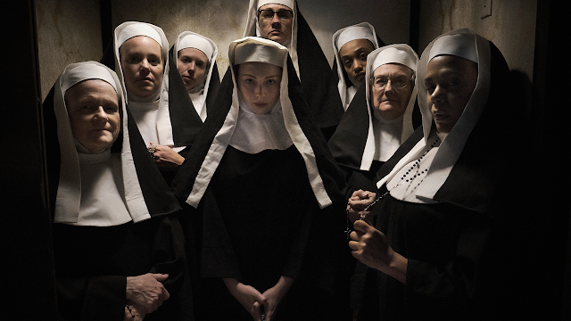 A group of nuns look at camera