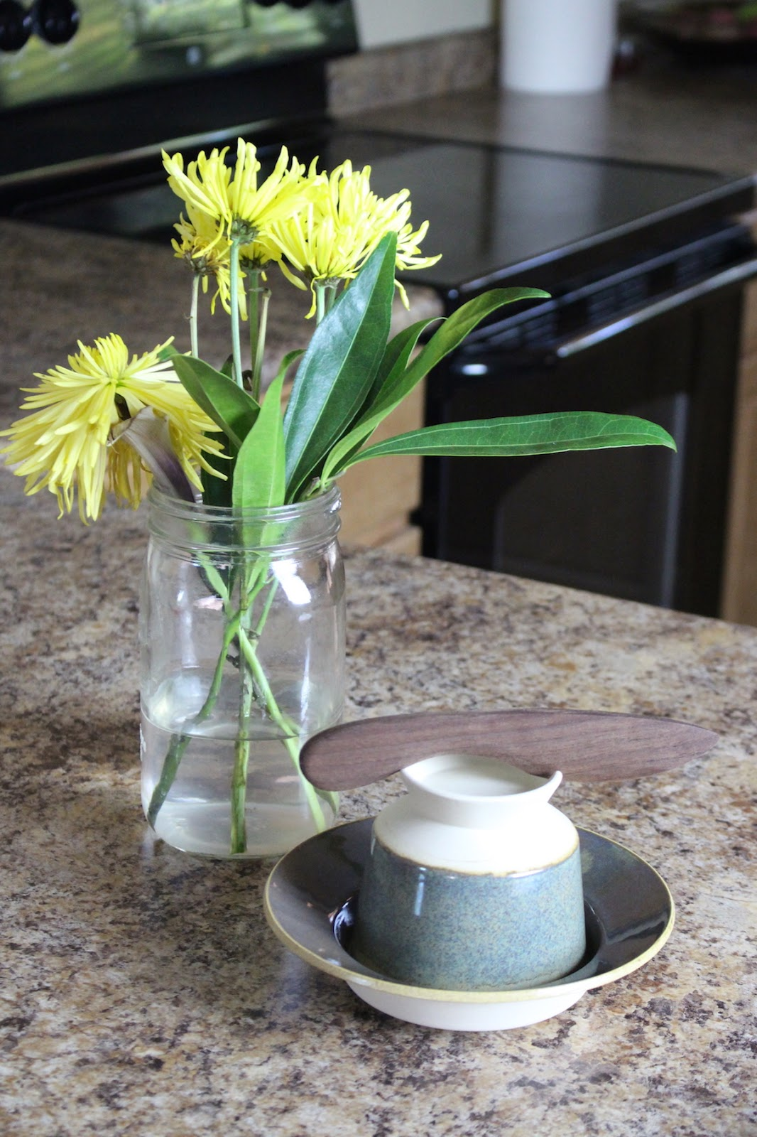 A close-up right side view of the kitchen featuring a unique butter crock from Uncommon Goods and some yellow flowers.