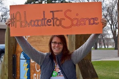 Photo of person holding sign saying hashtag Advocate For Science