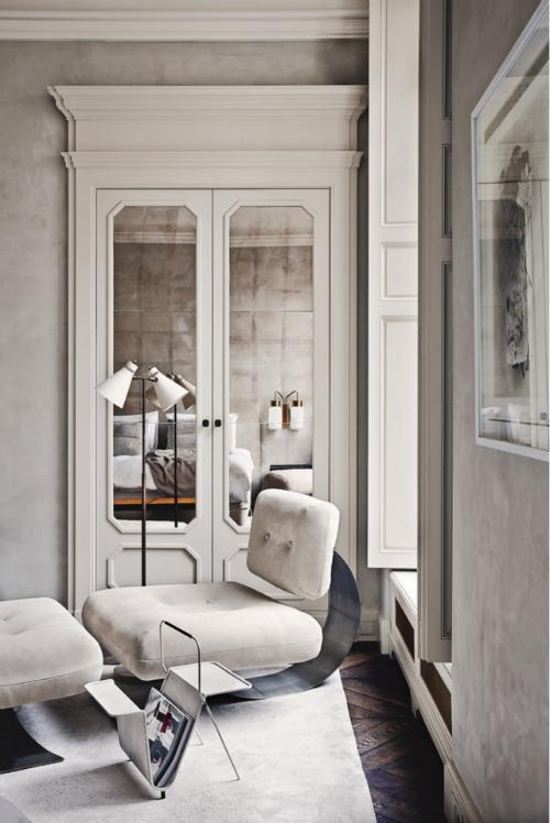 Ein weißer Sessel steht im Schlafzimmer, das mit in weiß gestrichen ist.