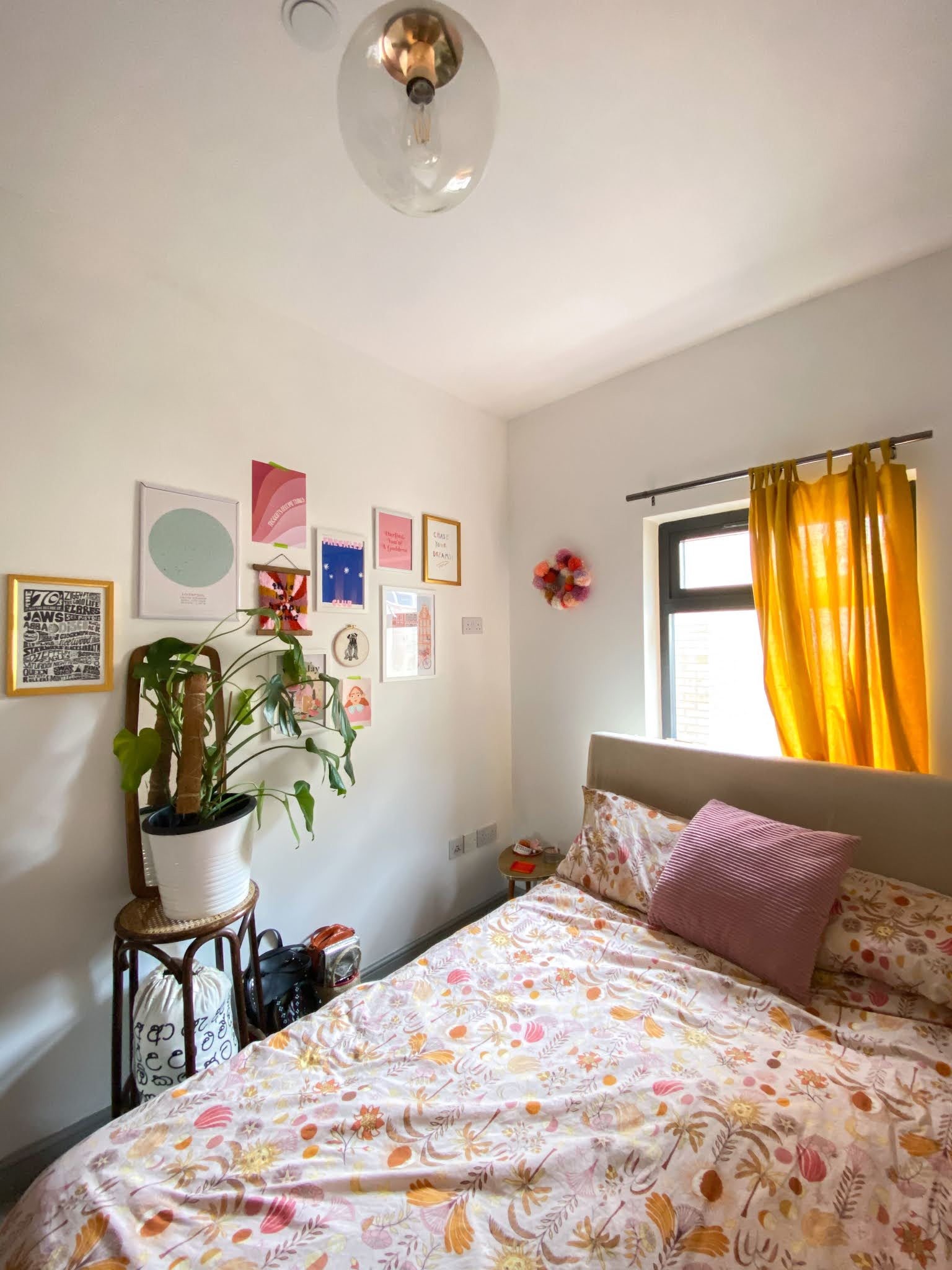 white walled bedroom with houseplants, gallery wall of bright prints, pink and mustard sun and moon print bedding and mustard yellow curtains