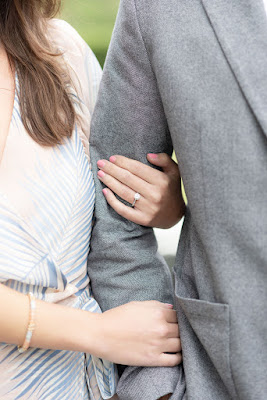 couple linking arms with engagement ring