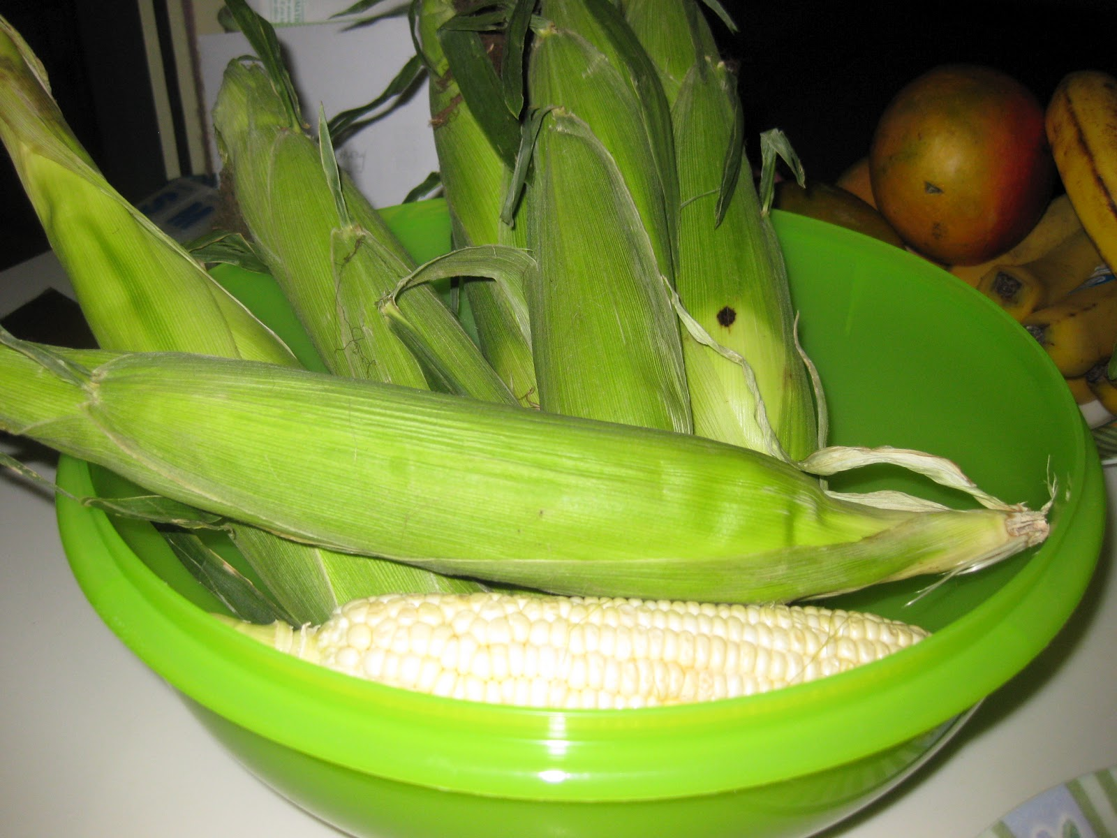 corn on the cob in its own jacket in a bowl