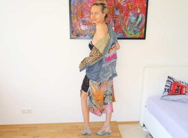 Model trägt Jeansjacke, bunten Seidenrock, High Heels, nackte Schulter