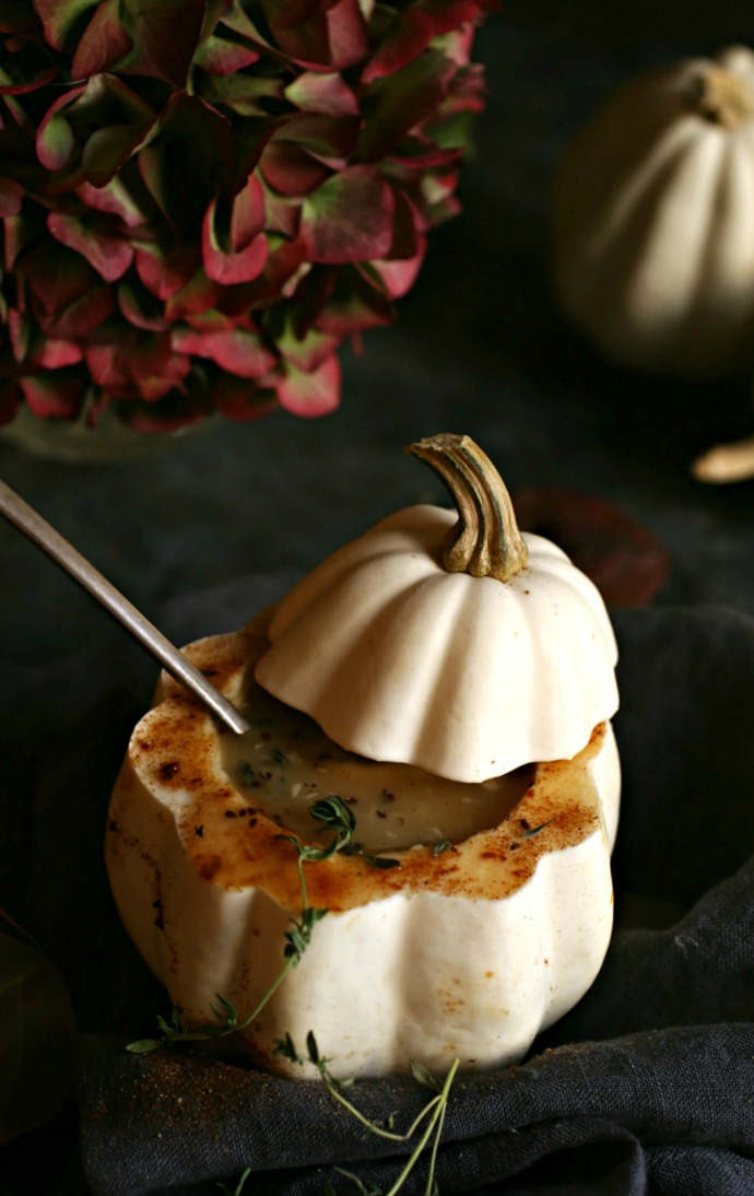 Recipe for a creamy acorn squash and potato soup, flavored with cumin and fresh thyme.