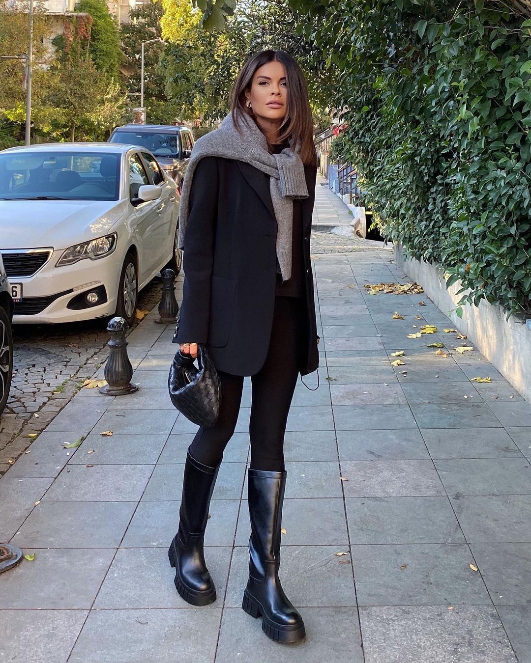 An Easy Way to Elevate Your Leggings —@nazifeeozcan outfit idea with a black blazer, gray sweater around the shoulders, black leggings and knee-high lug-sole boots