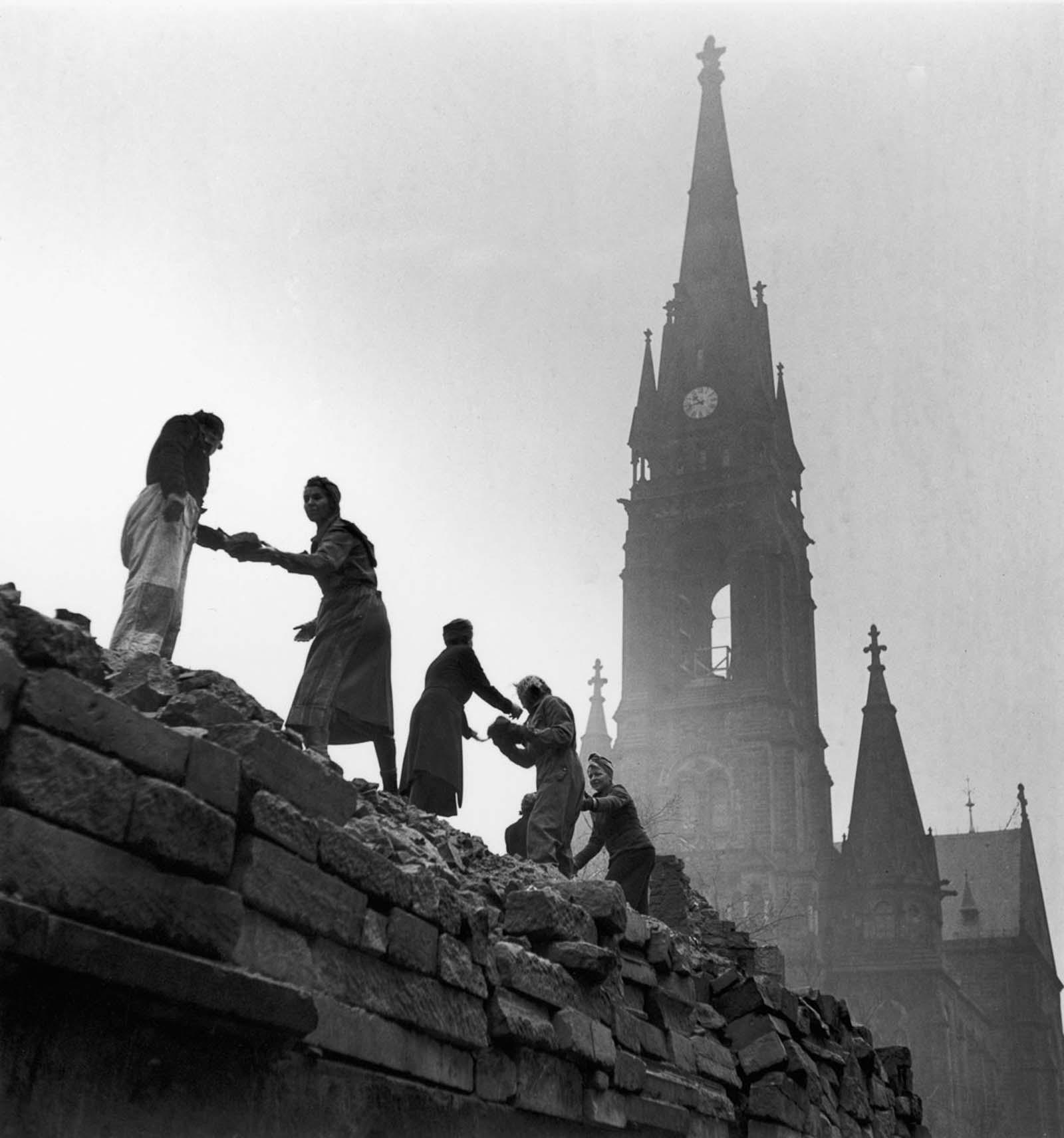 Women pass bricks atop a ruined building. 1946.