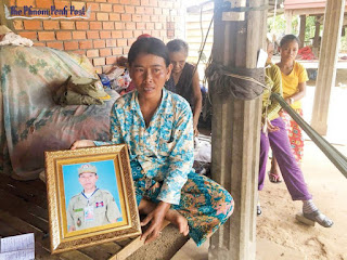 Hoeum Hout holds a portrait of her husband, Eout Ang, yesterday in Siem Reap's Angkor Chum district. Thik Kaliyann