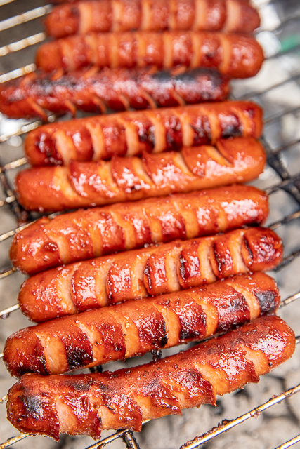hot dogs cooking on the grill