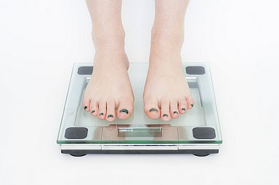 standing on a scale with a weight loss plateau