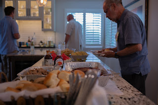 People enjoying food spread in a newly remodeled kitchen