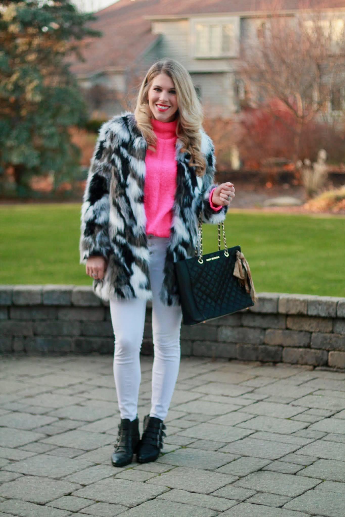 black white faux fur coat, pink tunic sweater, white jeans, black quilted tote, black buckle booties