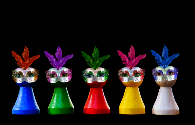 Five board game pawns, each wearing a Carnival/Mardi Gras mask with eyes looking out from them.