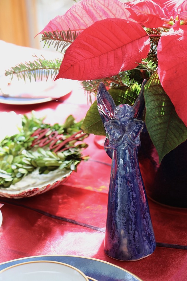 Touches of traditional Christmas green color are in the preserved boxwood on an angel wing plate and in the evergreens in the floral centerpiece of the Christmas Red and Navy Blue Table Setting
