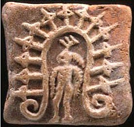 Harappan tree-spirit standing under an arch formed by the branch of a tree.