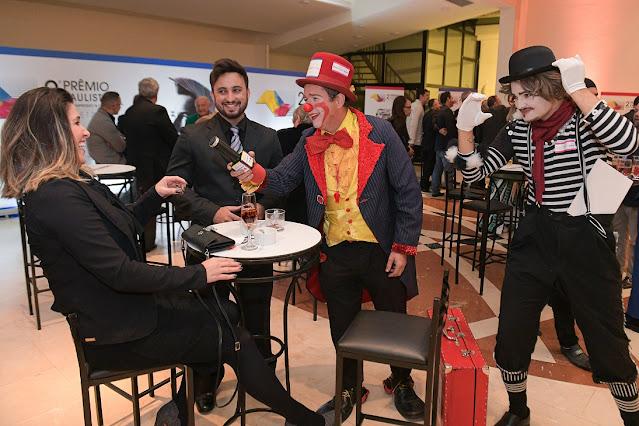 Recepção com artistas de Humor e Circo em evento de premiação Abigraf, na foto palhaço interagindo com convidados sentados em uma mesa.