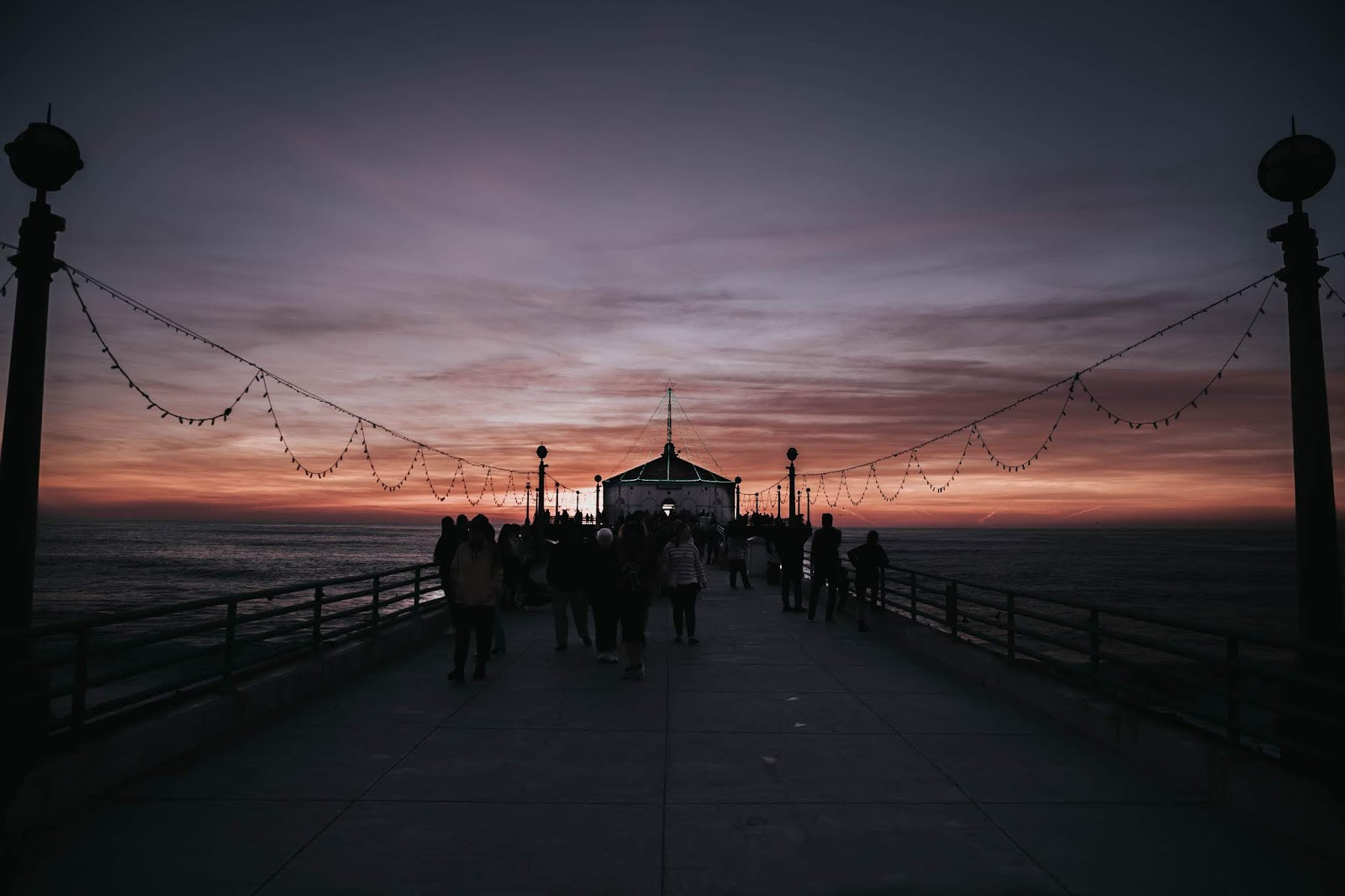 groups of people walk down a pier at sunset for a blog post about movie Dunkirk
