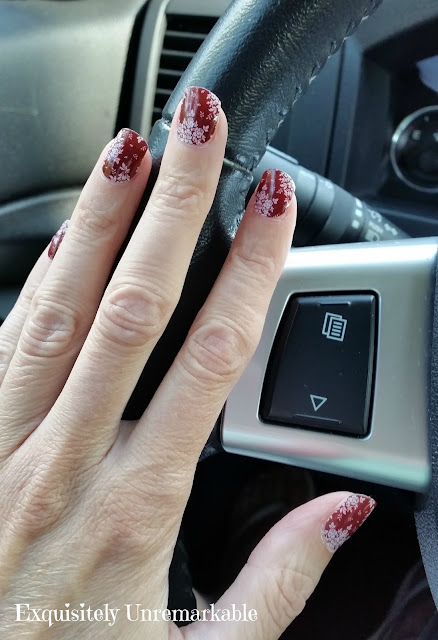 Red Floral Jamberry Nail Wraps on hand on steering wheel.