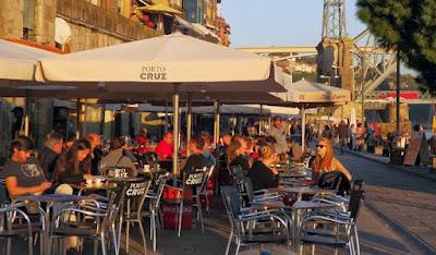 Esplanadas com pessoas sentadas ao sol na Ribeira do Porto